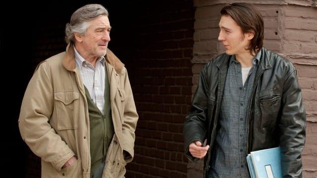 Ein älterer und ein junger Mann stehen nebeneinander und schauen sich an.