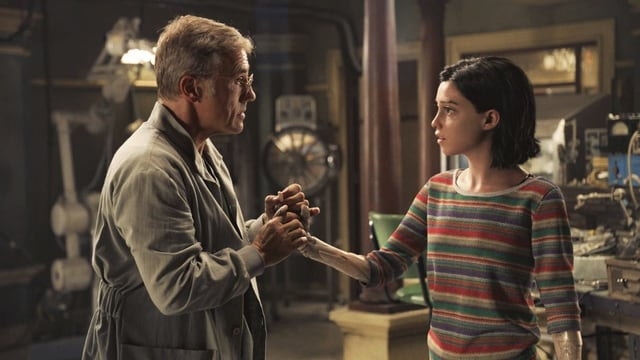 In einer Werkstatt: Ein Mann hält die Hand eines Mädchens.