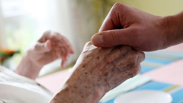 Jüngere Hand hält ältere Hand
