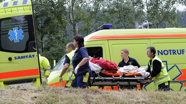 Sanitäter fahren einen verletzten auf der Bahre zum Krankenwagen