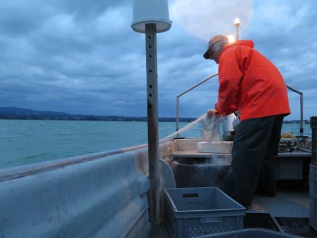 Mann im Boot zieht Netz ein.