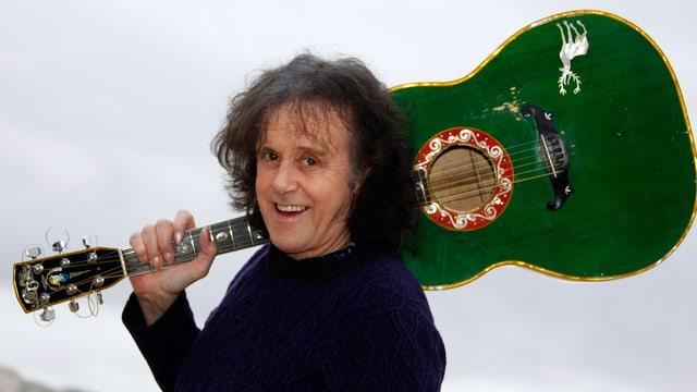 Portrait von Donovan, der seine grüne Gitarre auf der Schulter trägt.