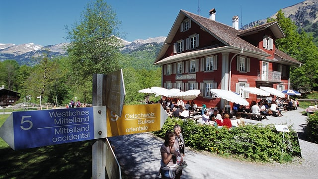Restaurant im Freilichtmuseum mit offener Gartenterrasse, Sonnenschirmen und einem Wegweiser davor.