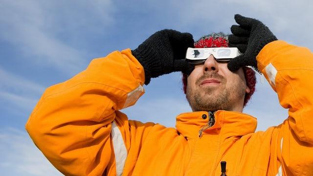 Ein Mann beobachtet durch eine Brille die Sonnenfinsternis