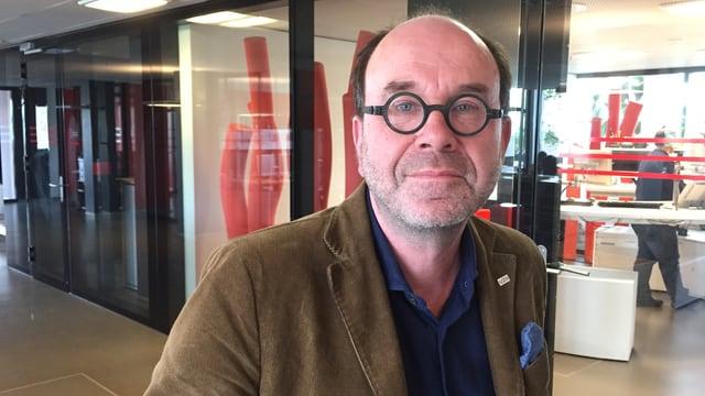 Mann mit runder Brille im Radiostudio