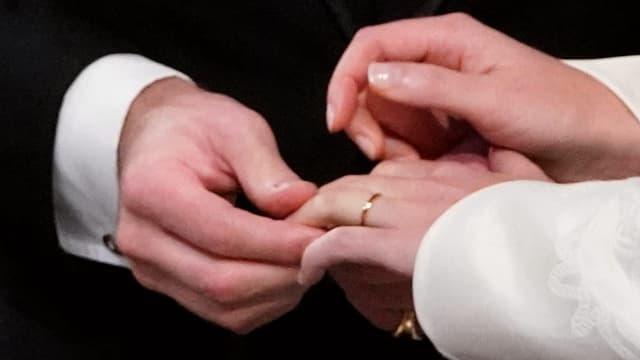 Männerhand hält einen Frauenhand, an der ein Ring steckt.
