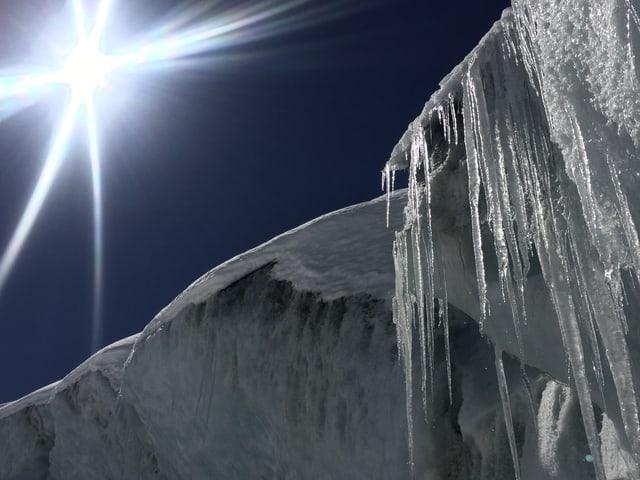 Blauer Himmel, Sonne links oben, rechts unten Eiszapfen mit Eisschild.