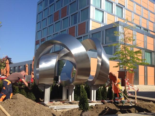 Arbeiter bauen Skulptur auf, Hotel im Hintergrund