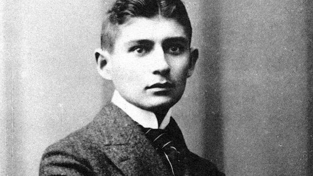 Porträt von Franz Kafka mit Anzug und Krawatte.