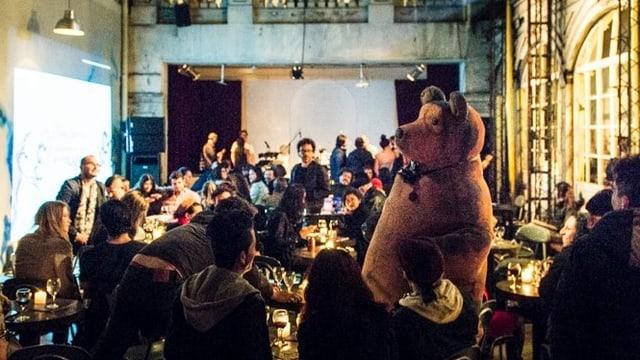 Ein Mann im Bärenkostüm steht in einem Saal mit vielen Leuten.