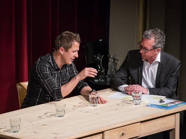 Männer sprechen an einem Tisch.