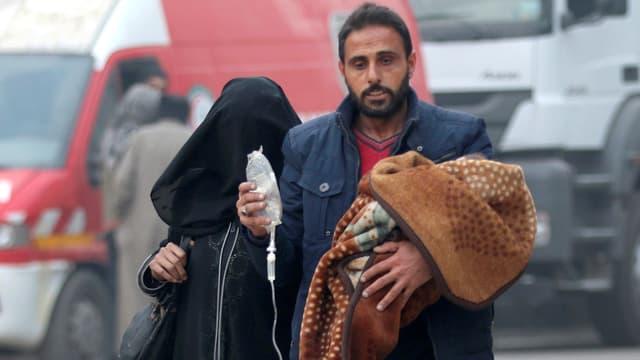 Ein Vater trägt ein in eine Decke gehülltes Kind, und die Infusion, an der es hängt, durch die Strasse. Ihnen folgt eine schwarz verhüllte Frau.