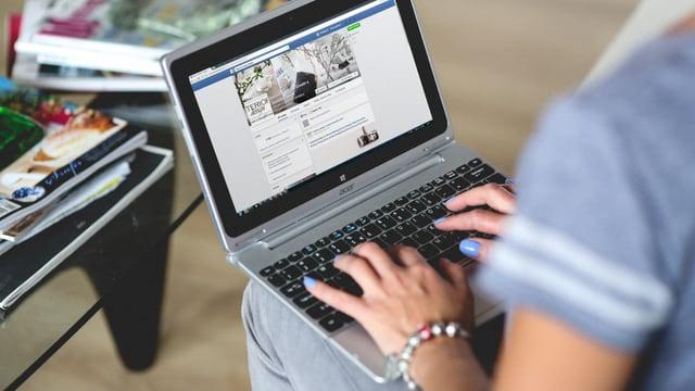 Frau tippt in ein Laptop auf ihrem Schoss.