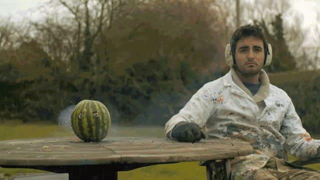 Eine Wassermelone explodiert rückwärts. Ein Mann sitzt traurig daneben.