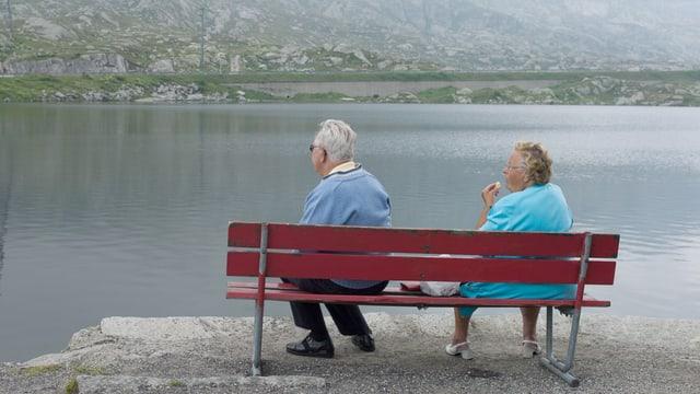 Ältere Frau und älterer Mann sitzen auf Bank an Gewässer.