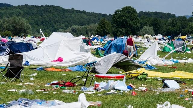 Wiese mit zerstören Zelten und haufenweise Abfall.