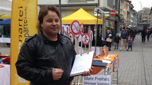 Mann mit schwarzer Lederjacke und Unterschriftenbogen