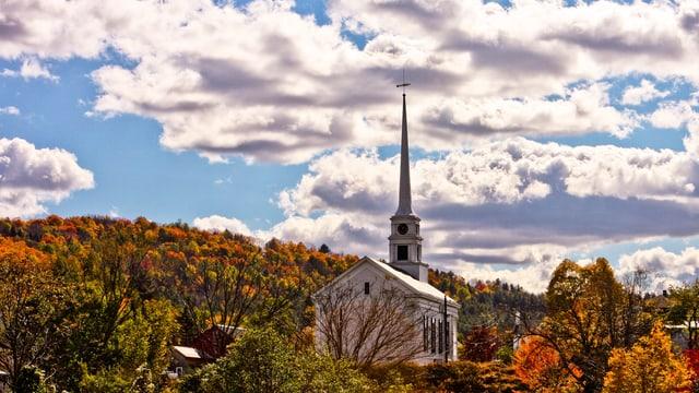 Ein Kirchturm, umgeben von einem Herbstwald, ragt in einen dramatisch bewölkten Himmel.