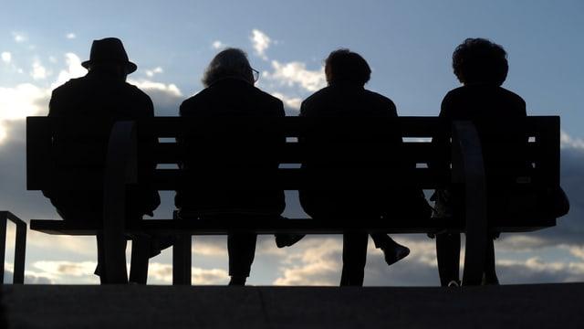 Man sieht vier ältere Personen auf einer Bank sitzen, dahinter der Himmel mit Wolken.