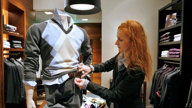 Eine Verkäuferin in einem Modegeschäft zupft die Kleider an einer Schaufensterpuppe zurecht.