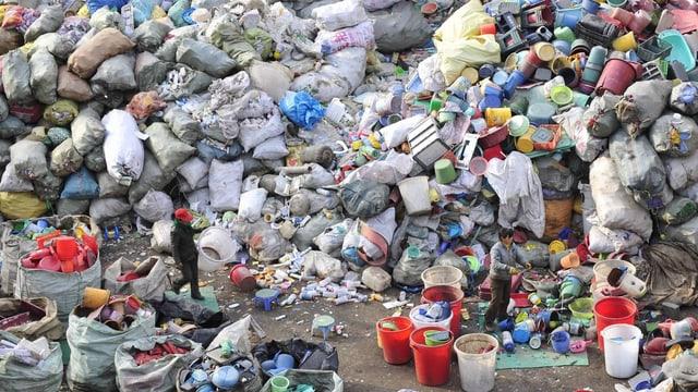 Riesehnaufen an Plastikgegenständen, ein Mann marschiert hindurch.