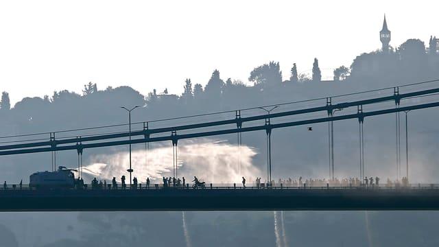 Ina part da la punt dal bosporus en silhouetta. Sin la punt in char armà che squitta aua lunsch sur ina fulla da persunas. Davostiers la silhouetta dad Istanbul.