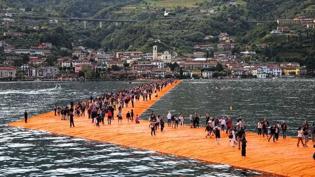 Leute spazieren über einen orangen Steg auf einem See.