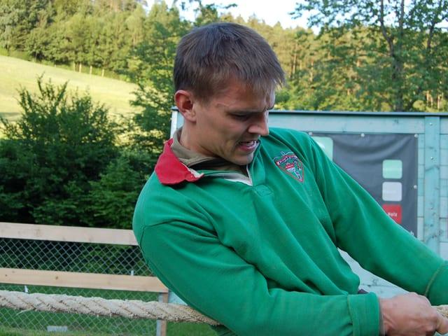 Ein Seilzieher in grüner Trainingskleidung mit angespannten Muskeln in Gesicht und Armen.