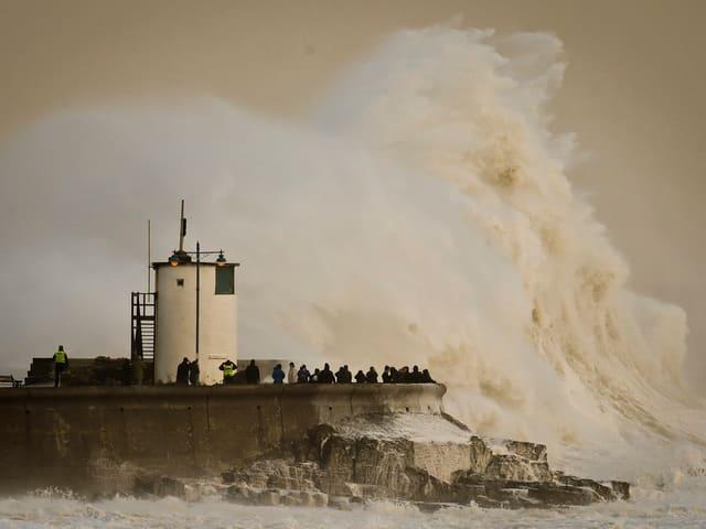 Leuchtturm an Küste, daneben meterhohe Welle. Menschen erscheinen verschwindend klein.
