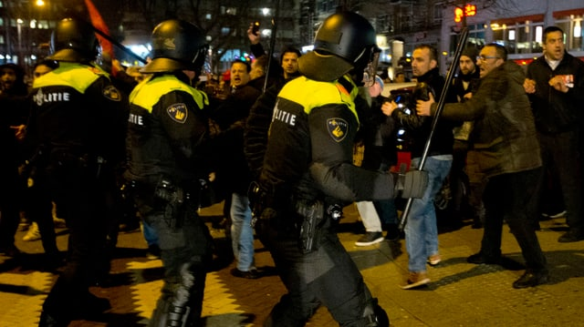 Polizisten mit Schlagstöcken vor Demonstranten.