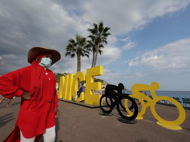 Eine Frau mit Maske vor einem Schild des Tour-de-France-Startortes Nizza.