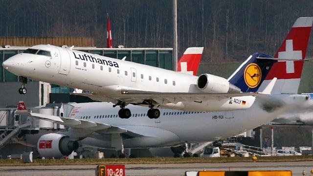 Startende Lufthansa-Maschine vor einem am Boden stehenden Swiss-Jet