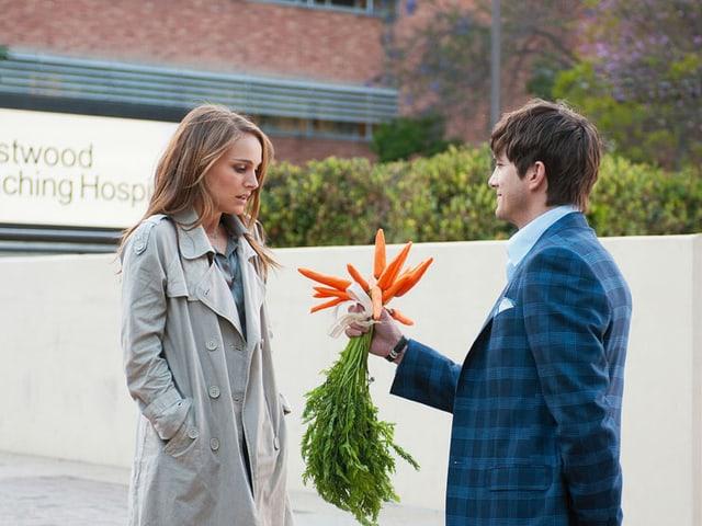 Asthon Kutcher als Adam überreicht Natalie Portman als Emma einen Bund Karotten.