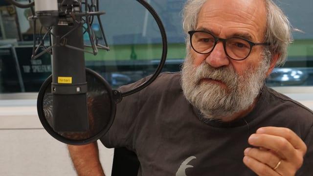 Mann mit Bart im Studio hinter Mikrofon.