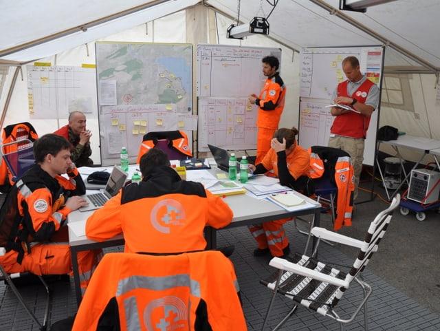 Hilfskräfte in orange-farbenen Kleidern arbeiten in einem weissen Zelt.