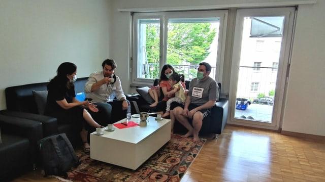 Personen sitzen auf Sofa und trinken Kaffee.