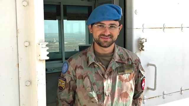 Mann mit blauem Beret ind Kampfanzug mit Abzeichen.