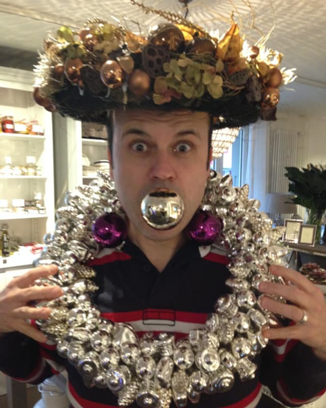 Der Moderator mit Weihnachtsschmuck auf dem Kopf, um den Hals und einer Weihnachtskugel im Mund.