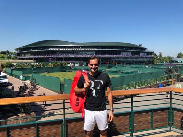 Roger Federer posiert vor den Plätzen in Wimbledon.