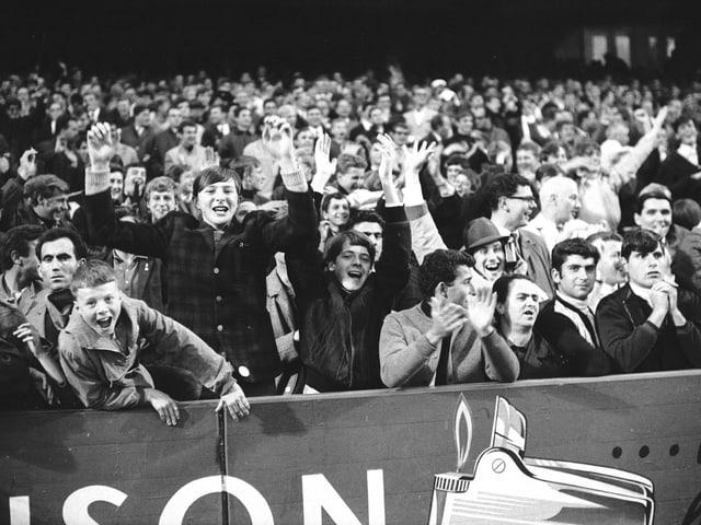 Publikum auf einer Zuschauertribühne in einem Fussballstadion.