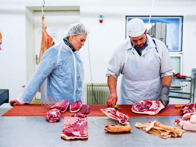Eine Frau und ein Mann in Plastik-Schutzkleidung stehen vor einer Schlachtbank, auf der Fleischstücke liegen.
