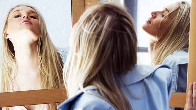 Eine junge Frau betrachtet sich in drei Spiegeln gleichzeitig.