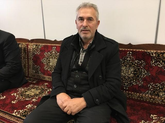 Mann sitzt auf einem Sofa
