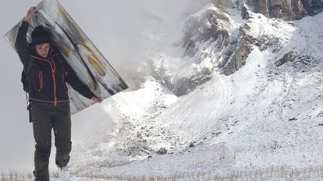Eine Frau schleppt ein grosses Gemälde durch eine verschneite Landschaft.