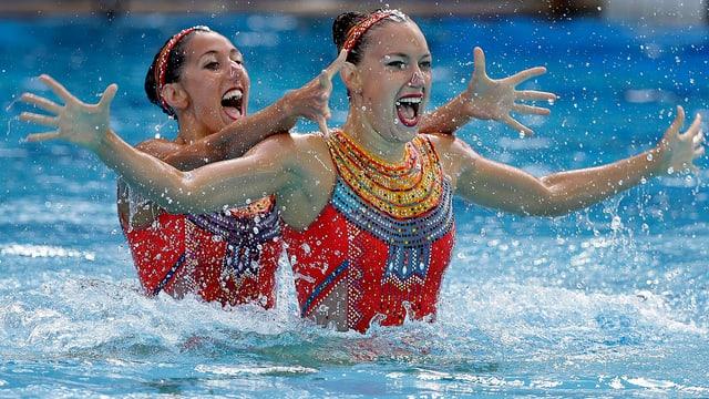 Synchronschwimmerinnen mit ausgestreckten Händen.
