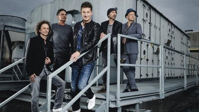 Die fünf Musiker und Sänger stehen auf einer Metalltreppe.