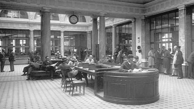 Schwarzweissaufnahme einer Bank-Schalterhalle um die Jahrhundertwende.