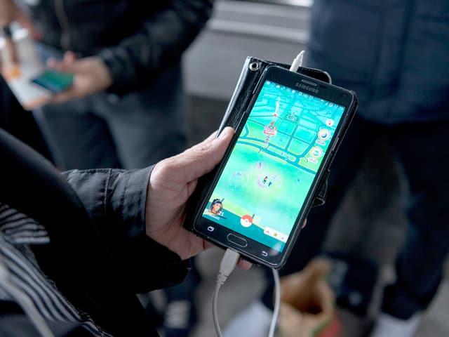 Eine ältere Person spielt «Pokémon Go».