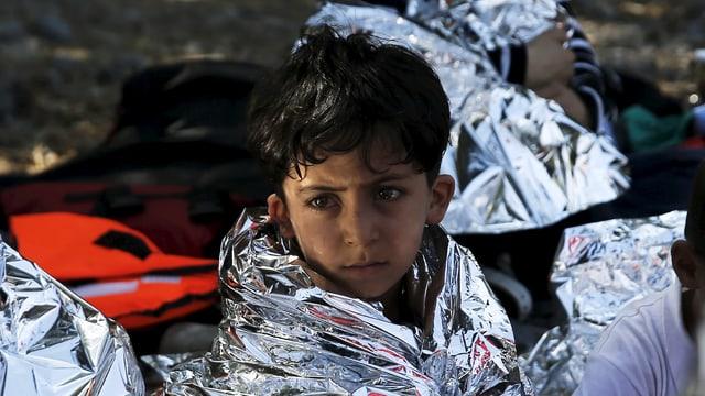 Ein Flüchtlingsjunge, der in eine Wärmefolie gewickelt ist