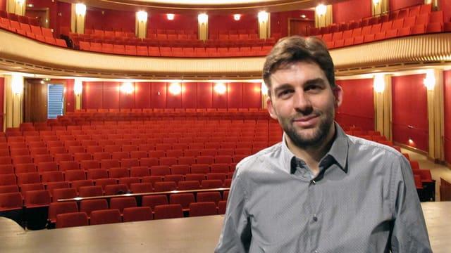 Mann mit grauem Hemd auf Bühne vor roten Besucherstühlen